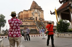 Chinese tourists have their photos taken at Wat Chedi Luang in Chiang Mai, Thailand.