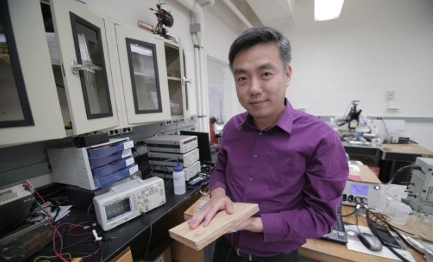 Associate Professor Xudong Wang holds a prototype of the researchers' energy harvesting technology, which uses wood pulp and harnesses nanofibers.