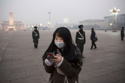 A Chinese woman looks at her phone as Chinese Paramilitary police wear masks to protect against pollution as they stand guard in heavy smog in Tiananmen Square on Dec. 9, 2015 in Beijing, China.