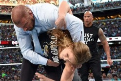 Ronda Rousey executes a Judo throw to Triple H as The Rock looks on at WrestleMania 31 last year.