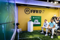 Ajax Amsterdam players Koen Weijland (L) and Jairo Riedewald play a game on an 'Xbox One' during the opening of the FIFA 17 Xperience in Amsterdam on September 22, 2016.