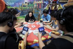 Attendees play video games on Nintendo Co.'s New 3DS LL in the Capcom Co. booth at the Tokyo Game Show 2016 at Makuhari Messe in Chiba, Japan, on Thursday, Sept. 15, 2016.