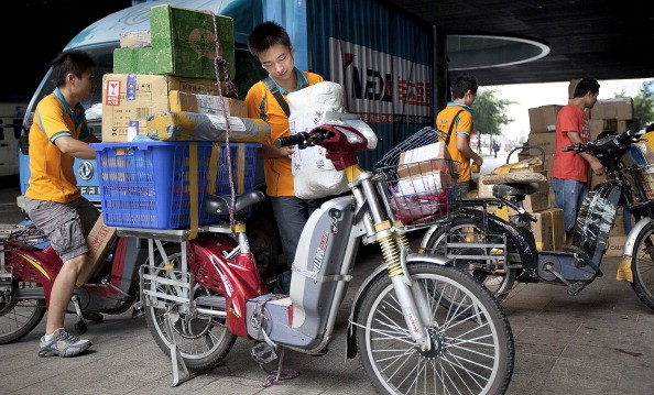 A courier loads packages for delivery using an electric bicycle in Shenzhen, Guangdong Province.