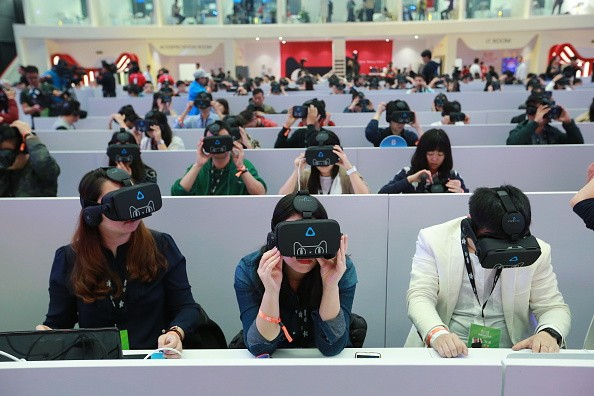 Members of the media wear virtual reality (VR) headsets to experiences VR shopping during Singles' Day.
