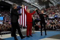 Democratic presidential nominee Hillary Clinton (C) raises her arms with musicians Jon Bon Jovi (L) and Lady Gaga during a campaign rally at North Carolina State University on November 8, 2016 in Raleigh North Carolina.