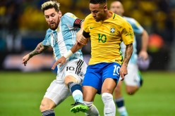 Brazil winger Neymar (R) competes for the ball against Argentina's Lionel Messi.
