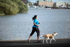 A woman runs with a dog on leash.