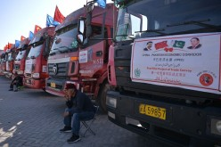 A Chinese worker waits near trucks carrying goods during the opening of a trade project in Gwadar port.
