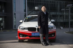 Wang Jing, Baidu's senior vice president, poses with one of the company's autonomous cars at Baidu's headquarters in Beijing.