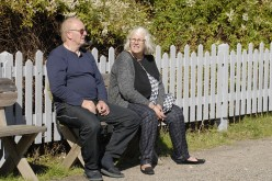 Retired senior couple seated in garden chairs appear relaxed looking out