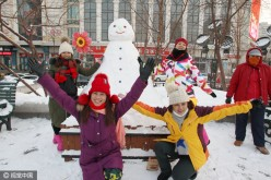 Visitors to Harbin pose for a photo with a snowman.