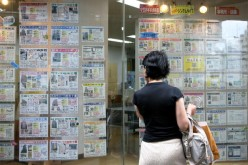 A woman looks at property details in front of a real estate agency on July 10, 2009, in Tokyo, Japan.