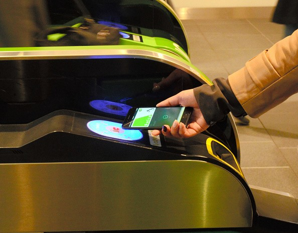 Commuter places iPhone 7 on the card reader to walk through a ticket gate