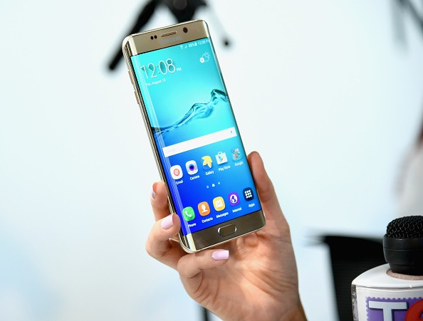 User holds Samsung Galaxy S6 edge+.