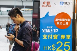 A man with a smartphone stands beside an advertisement for Alipay in a Hong Kong store.