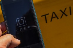 The smart phone app Uber logo is displayed on a mobile phone next to a taxi on July 1, 2014 in Barcelona, Spain.