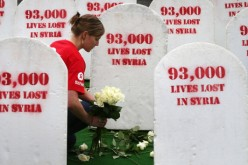 A social worker places roses among rows of gravestones symbolizing the 93,00 people killed in Syria, on June 17, 2013, in Belfast, Northern Ireland.