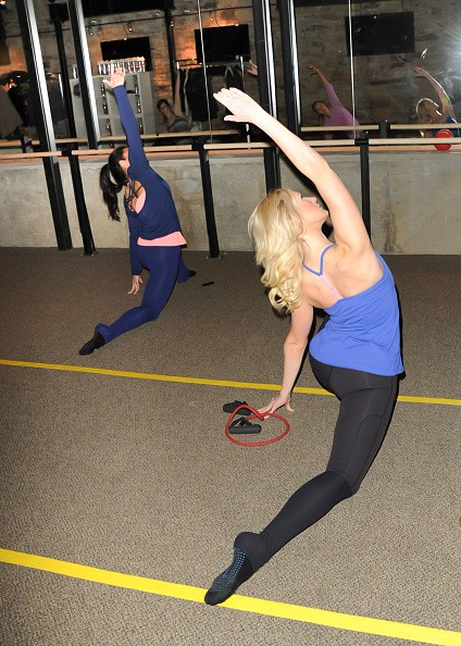 Two women are performing exercise routines in the gym to keep fit.