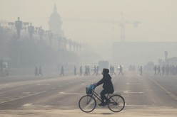 A woman wears a mask as she rides her bicycle along a street near Tiananmen Square on the third day of a red alert for pollution in Beijing.