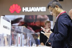 Visitors try out the Huawei Mate S smartphone at the Huawei stand at the 2015 IFA consumer electronics and appliances trade fair on September 4, 2015 in Berlin, Germany.