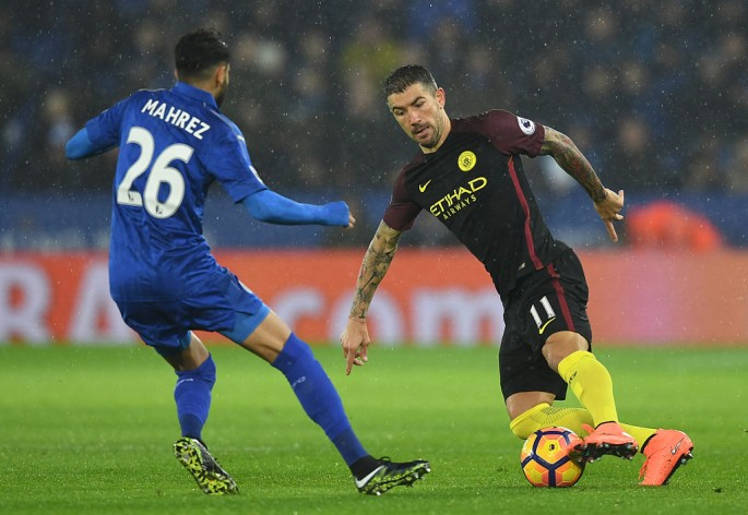 Manchester City defender Aleksandar Kolarov (R) goes against Leicester City's Riyad Mahrez.