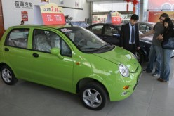 Customers view a small QQ model car at a showroom from a Chinese auto manufacturer.