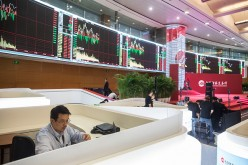 A man monitors stock changes on the electronic boards at the Shanghai Stock Exchange.