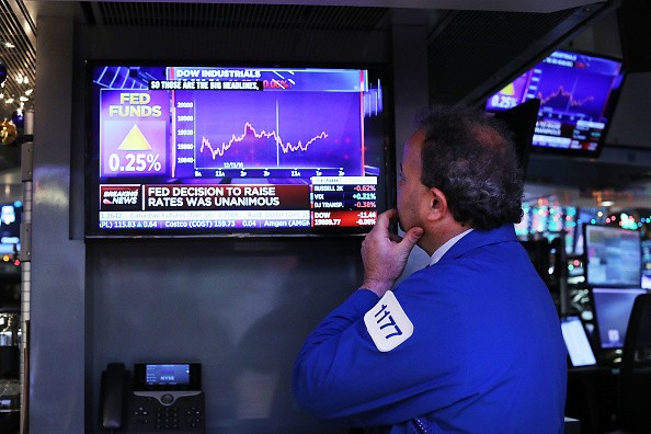 A trader at the New York Stock Exchange monitors the news as the Federal Reserve officials raised interest rates for the first time this year on Dec. 14.