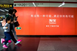 Commuters walk past a poster advertising Taobao services in a subway in Shanghai.