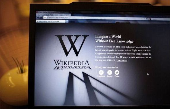 A laptop computer displays Wikipedia's front page showing a darkened logo on Jan. 18, 2012 in London, England.