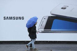 People walk past an advertisement for one of 2016's biggest tech releases: The Samsung S7 Edge.