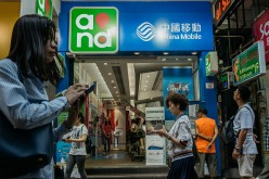 Pedestrians use their smartphones while walking past a China Mobile Ltd. store in Hong Kong, China.