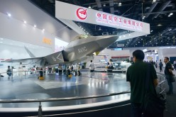 A man looks at a J-31 gyrfalcon stealth fighter plane model designed by Aviation Industry Corporation of China (AVIC) at the Beijing International Aviation Expo in Beijing.