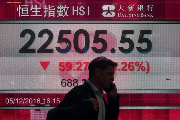 A man walks past a display board showing the Hang Seng Index during the first day of the Shenzhen-Hong Kong Stock Connect early this month.