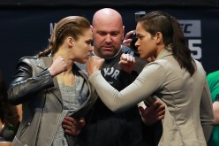 Amanda Nunes faces off against Ronda Rousey during the weigh-ins for their matchup.