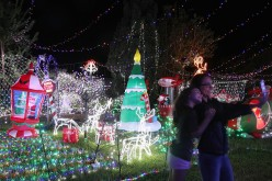 Visitors pose for a selfie as they view the Cambage Court Christmas Lights in the suburb of Davidson after the residents decorated their home and open the yard to visitors in celebration of Christmas.