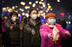 People wearing masks dance on a street, as red alert was released on December 16, warning that heavy smog would shroud the country's northern regions over the following two days.