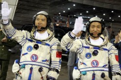Chinese astronauts Fei Junlong (L) and Nie Haisheng wave before boarding the Shenzhou VI spacecraft at Jiuquan Satellite Launch Center on October 12, 2005 in Jiuquan of Gansu Province, northwest China