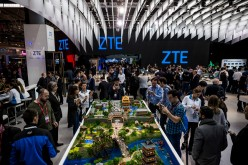Attendees visit the stand of ZTE during the second day of the Mobile World Congress 2016.