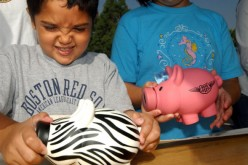 Michael Khatchadourina, 7, tries to open his piggy bank as he and his sister Krysta, 9, make a donation for victims of Hurricane Katrina at a daylong disaster relief collection event.