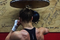 Ronda Rousey shows off her physique by posing in front of a speed bag at the gym she trains in.