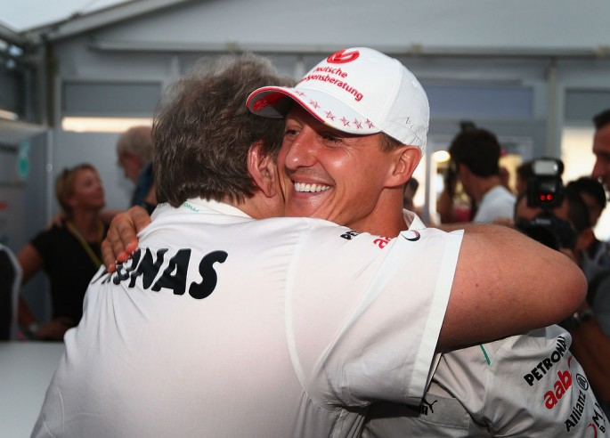 Michael Schumacher embraces Mercedes Motorsport President Norbert Haug after announcing his retirement.