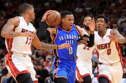 Russell Westbrook of the Oklahoma City Thunder drives on Josh Richardson and Rodney McGruder of the Miami Heat during a game at American Airlines Arena on December 27, 2016 in Miami, Florida.