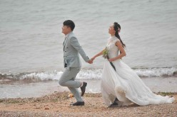 A couple takes wedding photos by the sea in Qingdao.