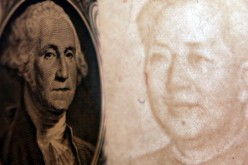 Details of dollar and a yuan notes are seen at a bank on May 15, 2006 in Beijing, China.