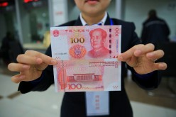 A bank staff shows the 100 yuan bill with new counterfeit features.