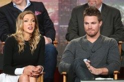 Katie Cassidy speaks as Stephen Amell listens onstage during the 'Arrow' and 'The Flash' panel as part of The CW 2015 Winter Television Critics Association press tour.