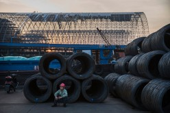 A worker takes a break as steel wire waits to be loaded onto barges in Changzhou, Jiangsu Province, on May 12, 2016.