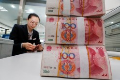A staff counts renminbi notes at a bank in Lianyungang, Jiangsu Province.