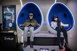 A Chinese couple wear virtual reality (VR) glasses in a VR arcade.